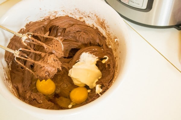 sour cream and eggs being mixed into a bowl of chocolate, cream cheese and sugar
