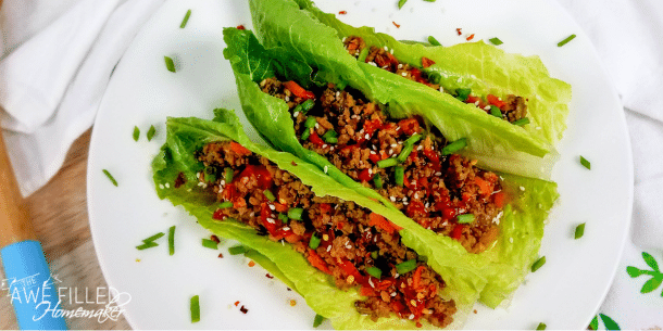 beef lettuce wraps on a white plate sprinkled with chopped green onions