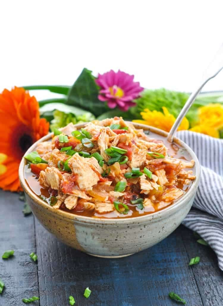 a bowl of Mexican chicken with a spoon in it on a brown table next to flowers