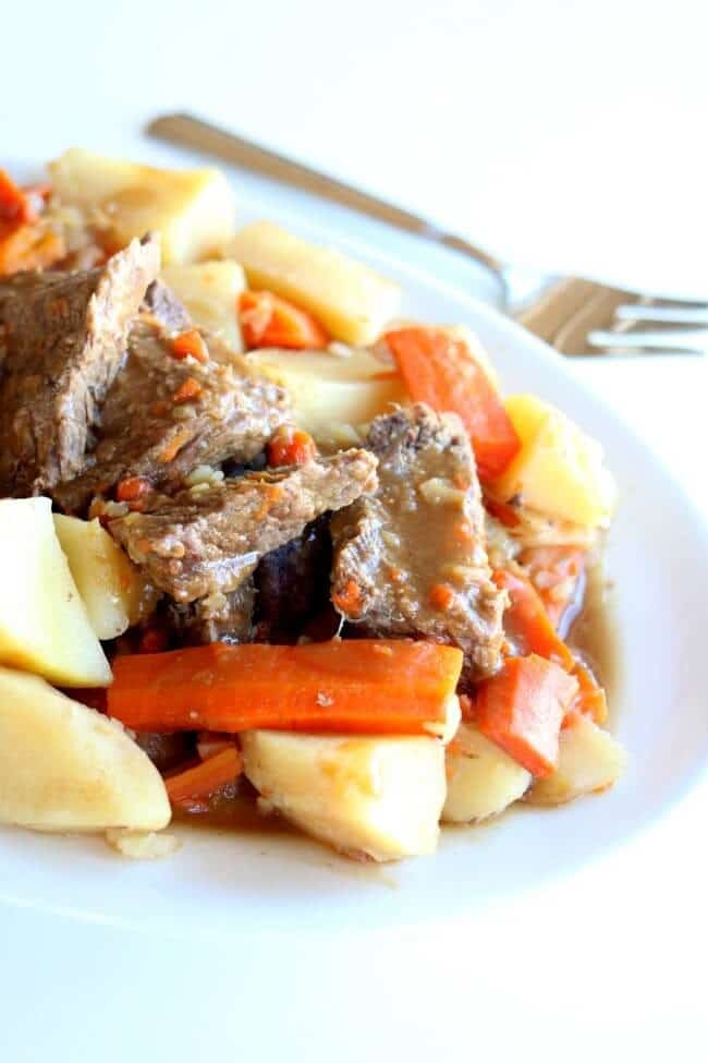pot roast dinner on a white plate with a fork next to it