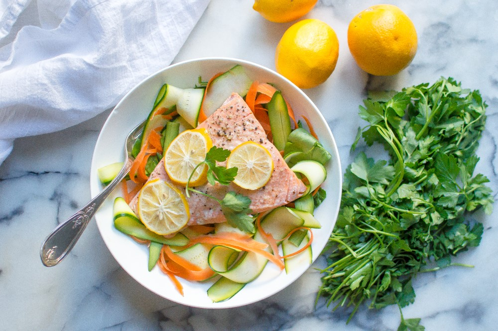 salmon topped with lemon and parsley and vegetables on a white plate with a fork with lemons and parsley next to it on a counter