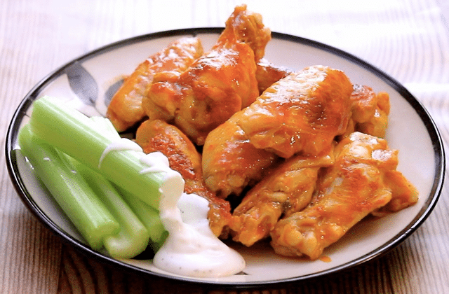 chicken wings and celery with sauce on a plate on a table