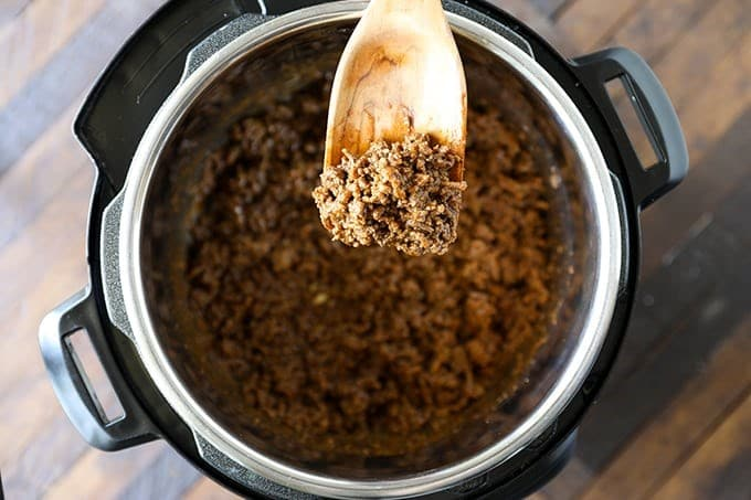 ground beef taco meat on a spoon above an instant pot filled with the beef