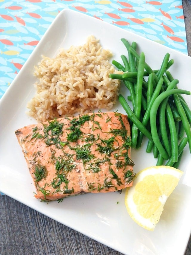 salmon, rice, green beans and a lemon slice on a white plate on a blue cloth