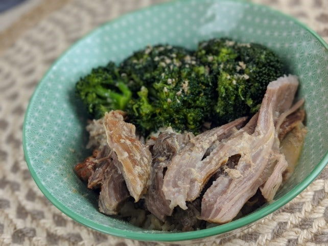 sliced pork roast and broccoli in a green bowl