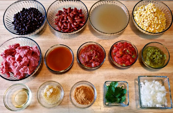 glass bowls of ingredients for instant pot taco soup, like beans, broth, vegetables, ground beef, sauce, tomatoes and seasonings