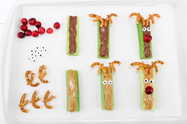 celery in various stages of being stuffed with peanut butter or nutella made to look like reindeer with pretzels as antlers, candy eyes, and cranberries for a nose