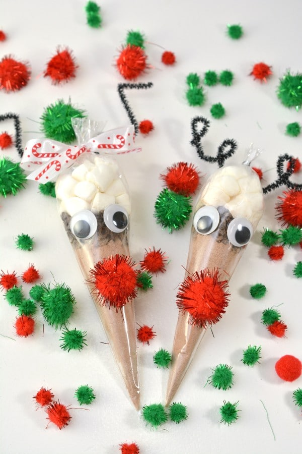 hot chocolate plastic gift bags in the shape of a reindeer with a red nose with more green and red pom poms on the table around them