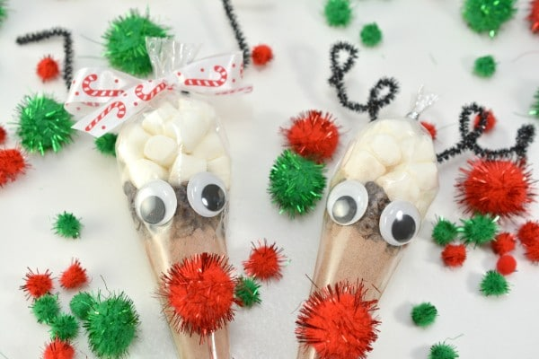 hot cocoa in a plastic bag shaped like a cone with a red pompom and googly eyes glued on it with more red and green pompoms on the table around them
