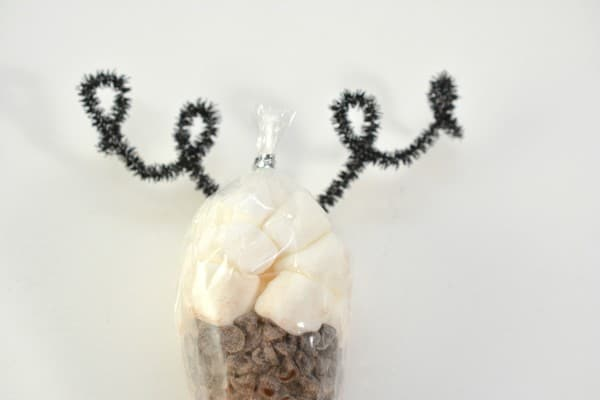 a cone shaped plastic bag with marshmallows and mini chocolate chips in it with a black pipe cleaner twisted at the top