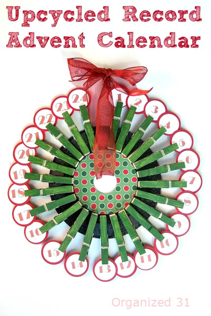 a green wreath made out of clothespins with numbered circles clipped on each one with title text reading Upcycled Record Advent Calendar