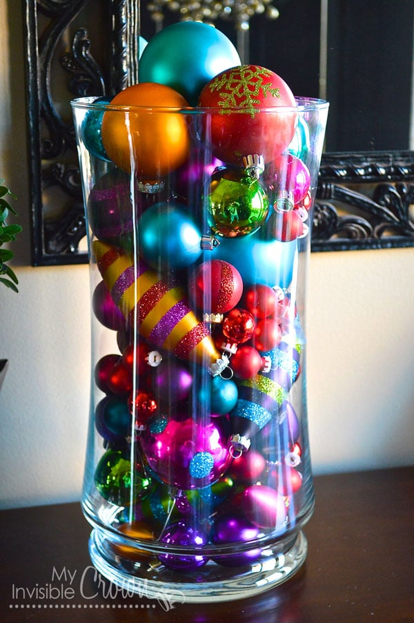 a glass vase full of Christmas ornaments on a table with a mirror in the background