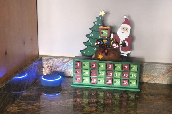 a wooden advent calendar box on a counter next to an amazon echo dot