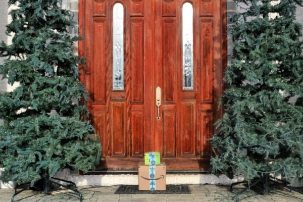 front doors of a house with christmas trees on both sides with amazon packages in front