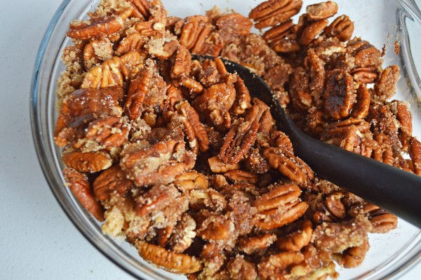 pecans coated with sugar cinnamon mixture in a glass bowl with a black spoon in it
