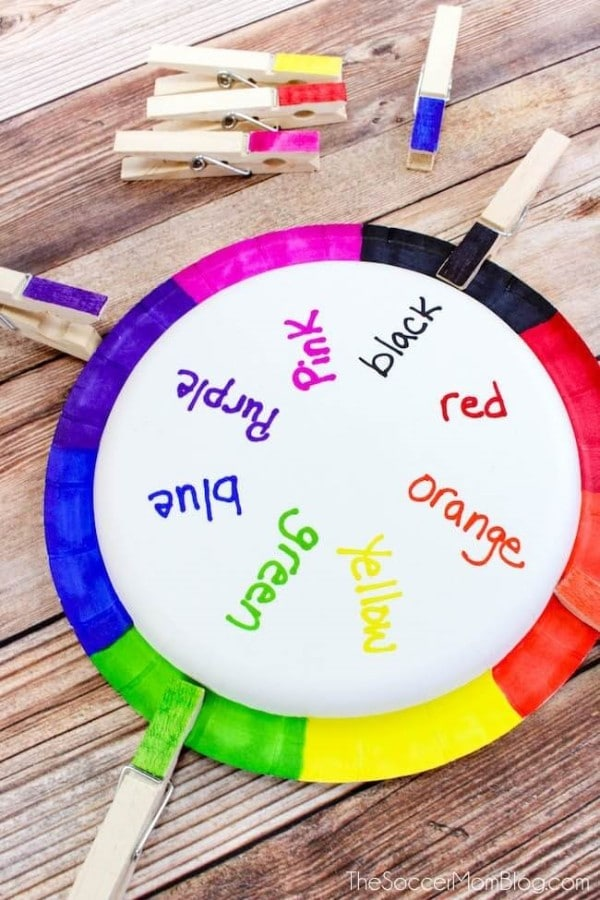 a multi-colored paper plate with color names written on it with colored clothespins clipped to the outside and on the table next to it