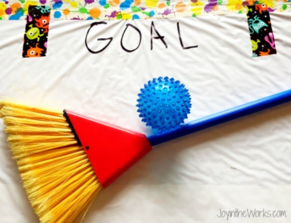 a broom and a ball on a plastic tablecloth with the word Goal written on it