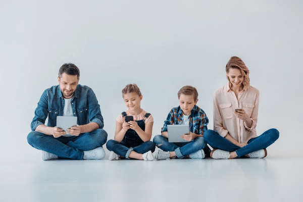 a mom, dad and two kids sitting on a white floor looking at tablets and cell phones