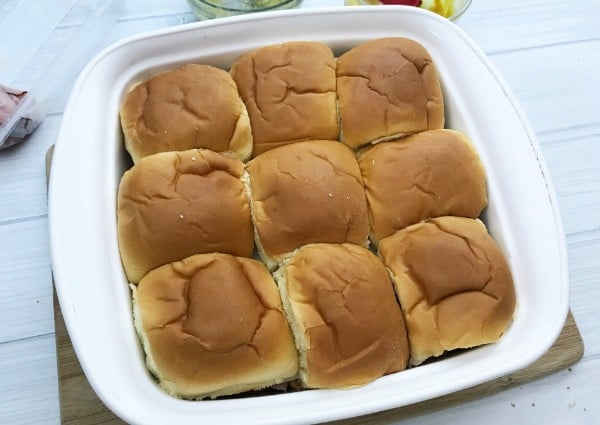 hawaiian roll ham and cheese sliders in a white dish on a white table