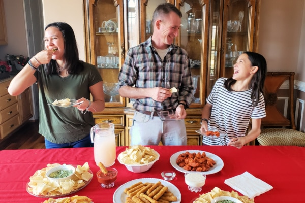 a dad and two girls eating food with a table covered by a red tablecloth with party food on it in front of them and a china cabinet in the background