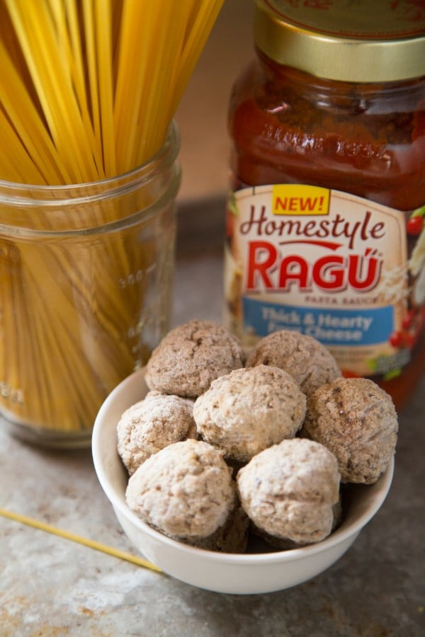 a jar full of spaghetti noodles, a white bowl of frozen meatballs, a jar of ragu pasta sauce