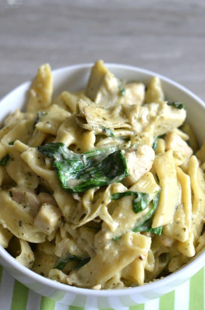spinach and artichoke pasta in a white bowl