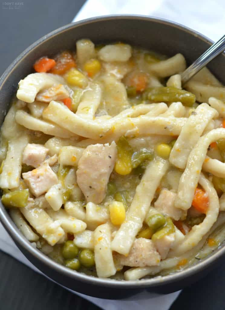 a bowl of chicken and noodles with a spoon in it