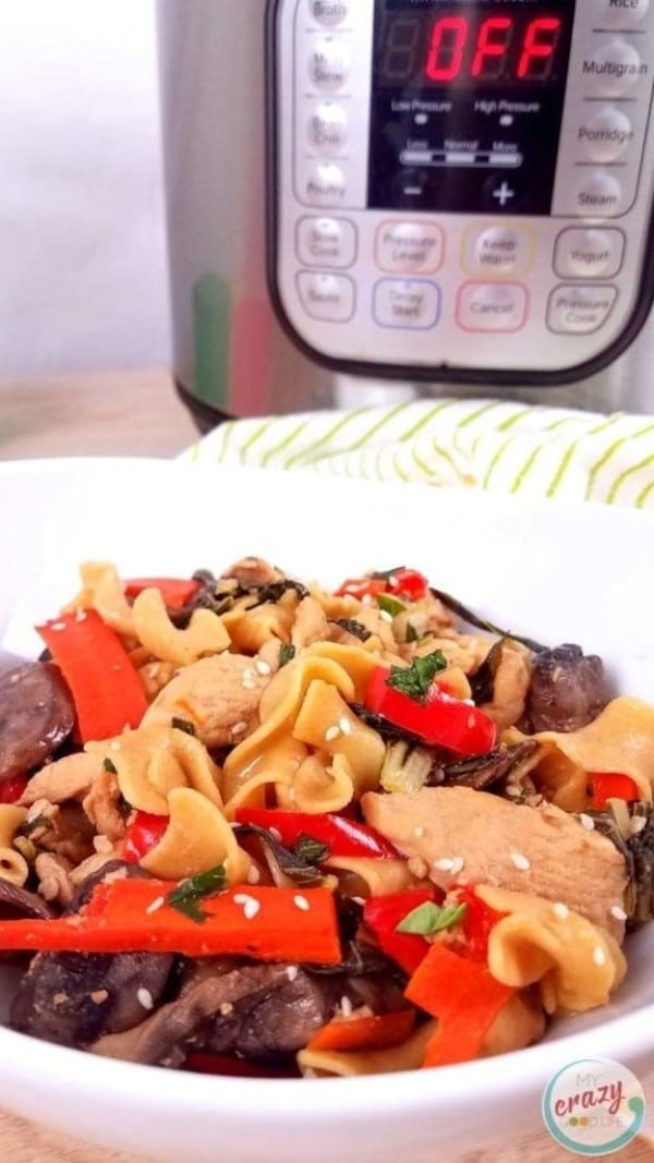 noodles, meat, and peppers in a white bowl with an instant pot in the background