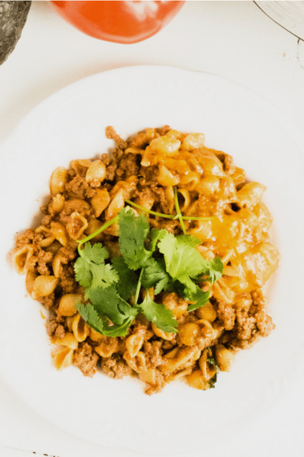 cheesy taco pasta topped with parsley on a white plate