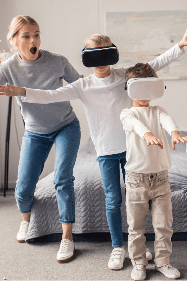 two kids wearing virtual reality glasses with the mom watching in a bedroom