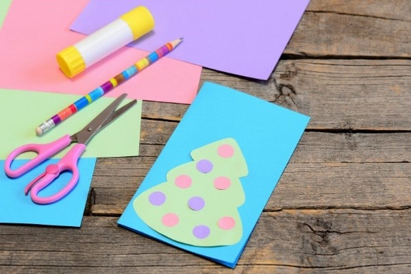 colored paper, glue stick, pencil, scissors on a table next to a paper christmas tree