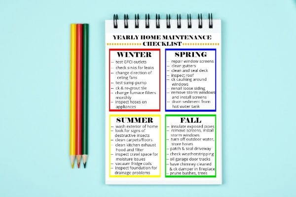 printable Yearly Home Maintenance Checklist next to colored pencils on a light green background