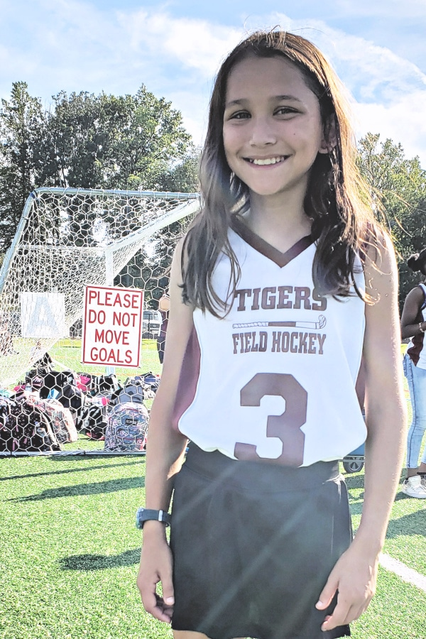 a girl in a field hockey uniform with a goal net in the background