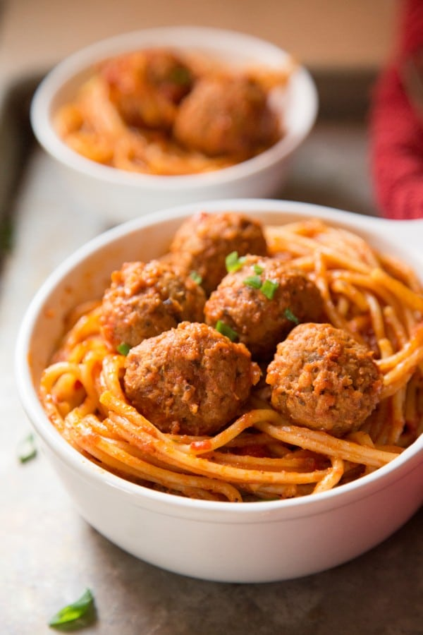a bowl of spaghetti and meatballs with another bowl in the background