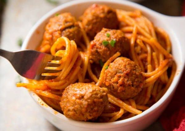 a white bowl of Spaghetti and Meatballs on a table with a fork in it