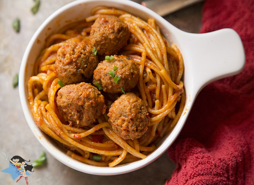 a white bowl of Spaghetti and Meatballs on a table with a red cloth next to it