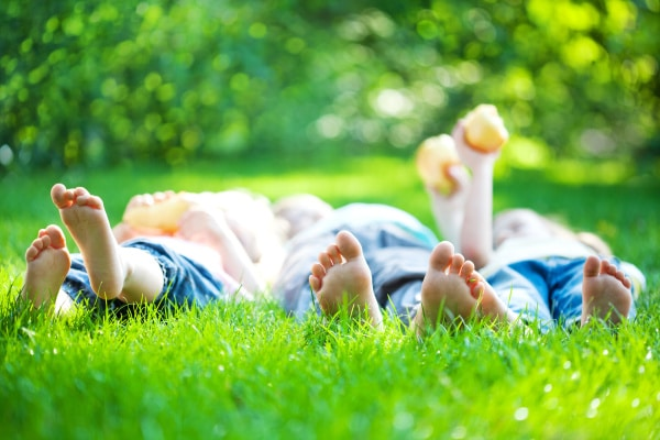 children laying down on the grass with their feet as the main view