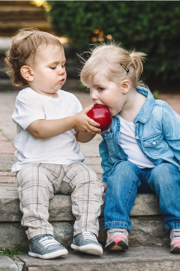 a little boy sharing a bite of his apple with a little girl, they're both sitting on a step outside