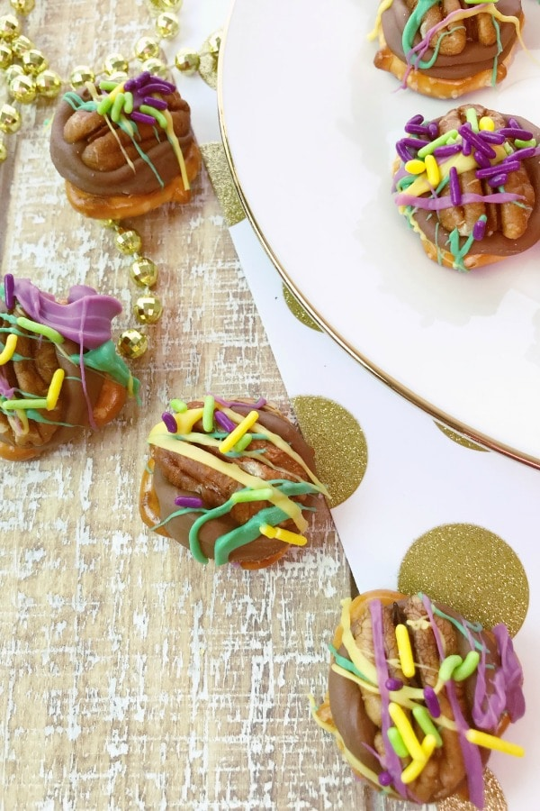 pretzels topped with chocolate, a pecan, purple frosting and colored sprinkles, on a white plate and on a gold tablecloth