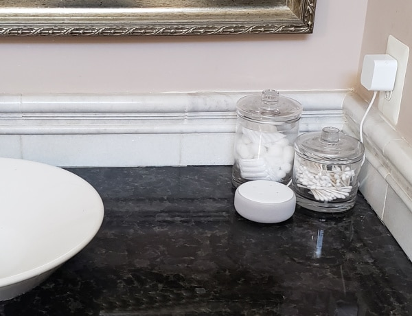 a bathroom counter with a sink basin, amazon echo, jars of cotton and qtips