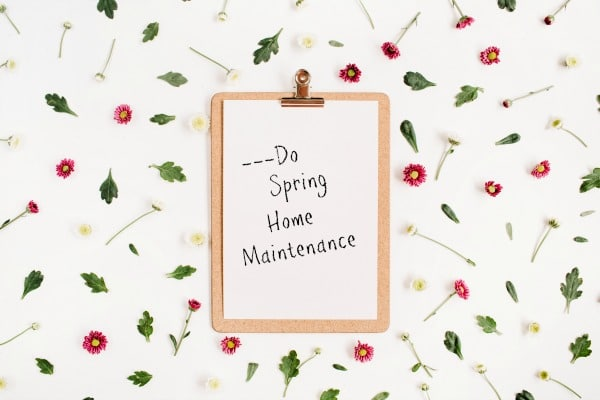 a paper with the words Do Spring Home Maintenance on a clipboard on a white background with flowers and leaves