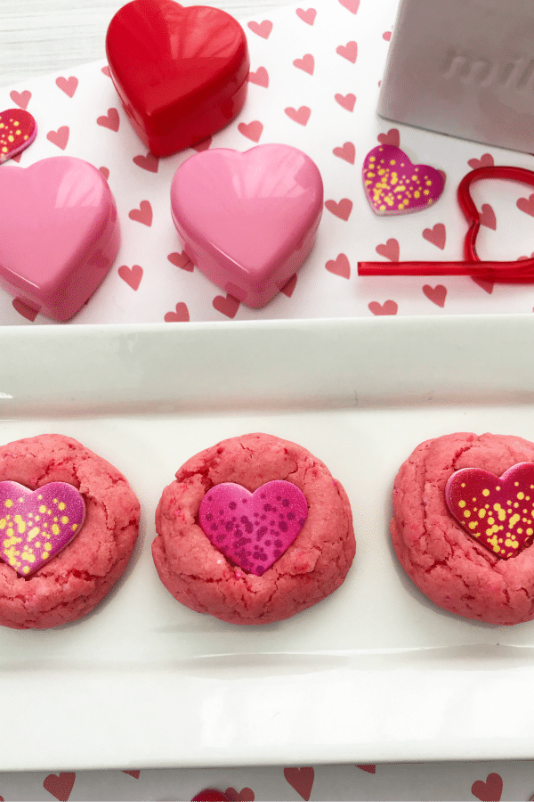 Strawberry Candy Heart Cookies on a tray on heart paper with plastic hearts and stickers next to it