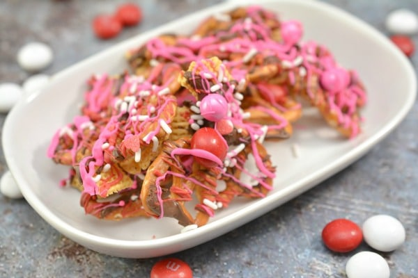 Valentine Bark in a white dish, which is a mix of chex, pretzels, melted chocolate, white sprinkles, and pink and white candy