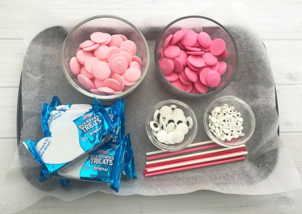 a tray with glass containers of pink candy melts and candy eyes, rice crispie treats and sticks