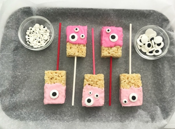 a tray lined with parchment paper with Valentine Rice Krispie Bars with pink frosting and monster candy eyes on a plate with more in the background