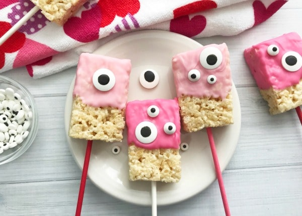 Valentine Rice Krispie Bars with pink frosting and monster candy eyes on a plate with more in the background on a heart cloth