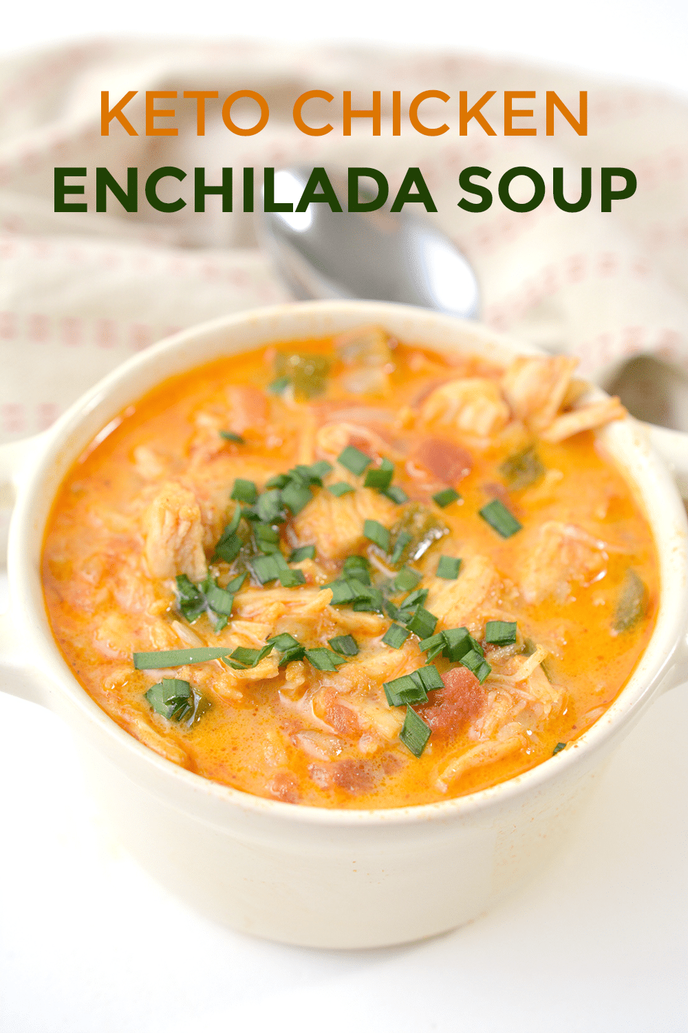 chicken enchilada soup in a white bowl on a white table with a spoon and cloth in the background with title text reading Keto Chicken Enchilada Soup