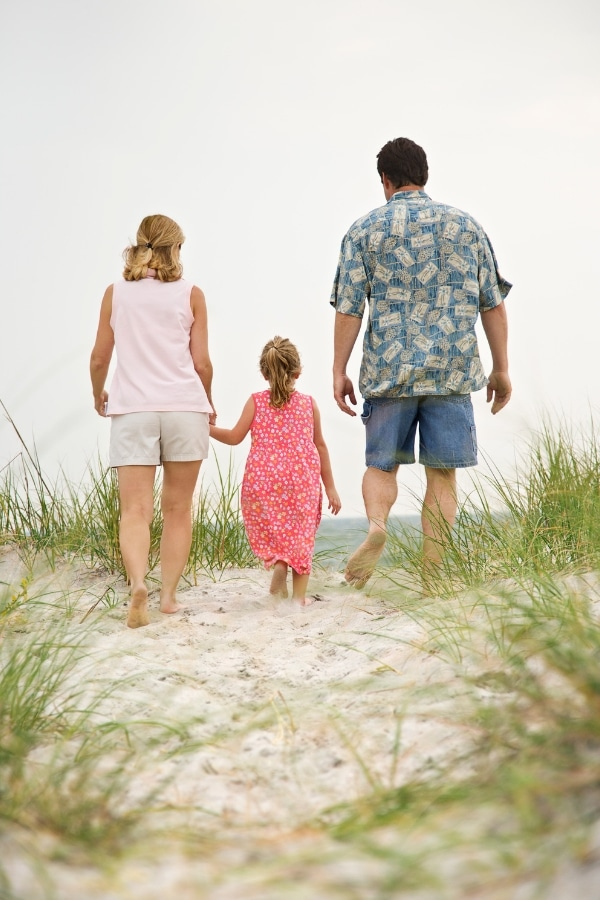 a mom holding a girl's hand and a dad next to them walking on the sand