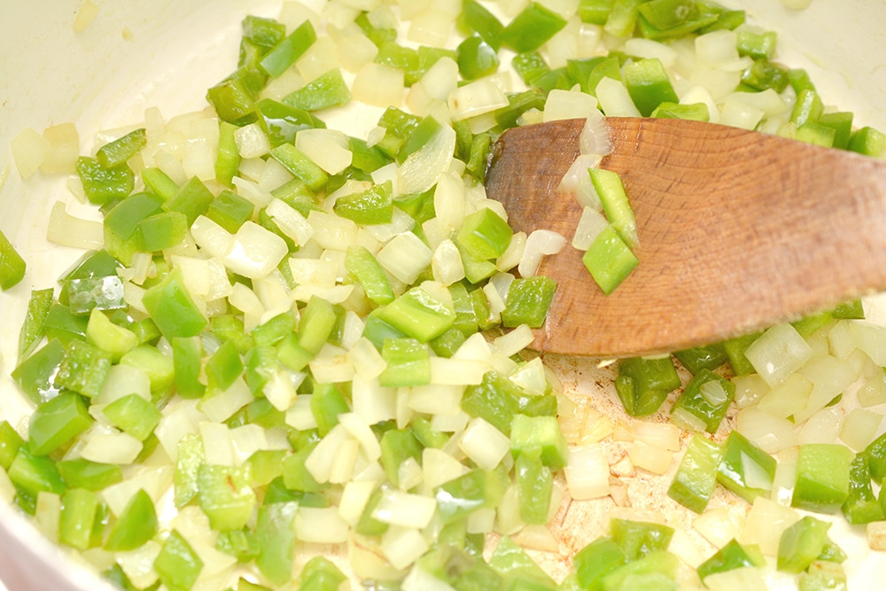 chopped onions and peppers in a pot with a wooden spoon