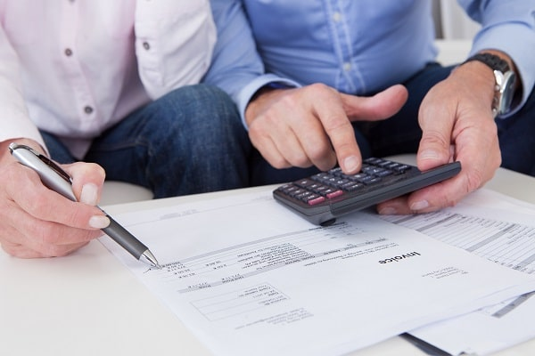 two people looking at invoices on a table with a pen and a calculator in their hand